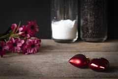 Red plastic hearts placed on a wooden table There is a flower placed on the left back and there are stock images