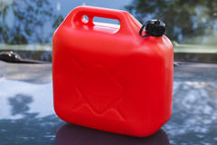 Red plastic jerry can stands on car hood Royalty Free Stock Photography