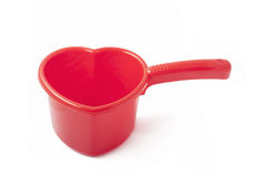 Red plastic ladle similar to a heart. On white background Royalty Free Stock Photos