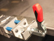 Red plastic lever of an industrial mechanical clamping device Royalty Free Stock Images