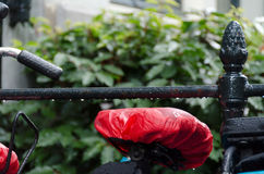 Red plastic protecting a bike seat from rain in Amsterdam Royalty Free Stock Images