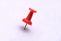Red Plastic Push Pin. One red plastic push pin or tack stuck into a white background Stock Image