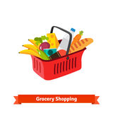 Red plastic shopping basket full of groceries Stock Photo