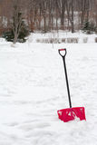 Red plastic shovel with black handle stuck in fluffy snow. Stock Images