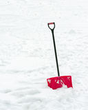 Red plastic shovel with black handle stuck in fluffy snow. Royalty Free Stock Photos