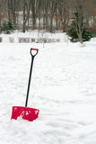 Red plastic shovel with black handle stuck in fluffy snow. Royalty Free Stock Photo