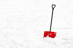 Red plastic shovel with black handle stuck in fluffy snow. Royalty Free Stock Images