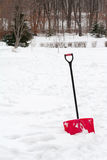 Red plastic shovel with black handle stuck in fluffy snow. Stock Image