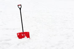 Red plastic shovel with black handle stuck in fluffy snow. Stock Photos
