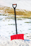 Red plastic shovel for snow removal. Royalty Free Stock Photo