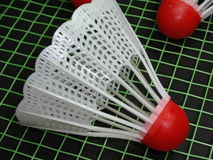 Red plastic shuttlecocks on badminton racket Royalty Free Stock Photo