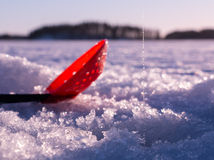 Red plastic skimmer scoop laying on ice with ice fishing line Stock Photo