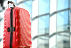 Red plastic travel suitcase in the airport hall Royalty Free Stock Image
