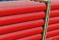 Red plastic tubes in the warehouse. Tubing. Red plumbing pipe plastic pvc close-up Royalty Free Stock Images