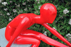 Red plastic woman sculpture. Blooming tree background. Stock Photo