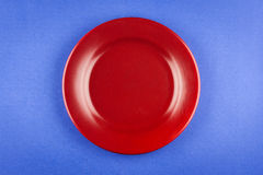 Red plate on blue table Stock Images