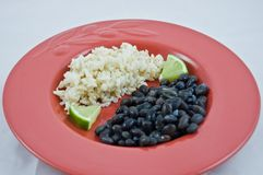 Red Plate of Brown Rice and Black Beans with Lime Stock Photography