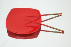 Red plate and chopsticks  on reflective background. Red plate and chopsticks on reflective background Stock Photo