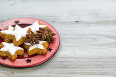 Red plate with cinnamon star cookies and anise stars Stock Photos