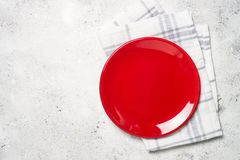 Red plate, cutlery and tablecloth on light stone table. Top view, copy space stock photos