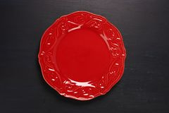 Red plate on dark background. Empty red ornate plate on dark wood background Royalty Free Stock Photography