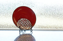 Red Plate Displayed On Stand On Counter Stock Photo