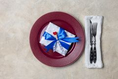 Red plate with gift box, with fork and knife at white background. Romantic gay dish wear stock image