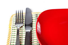 Red plate, knife and fork isolated on white Royalty Free Stock Image
