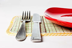 Red plate, knife and fork isolated on white Royalty Free Stock Photography