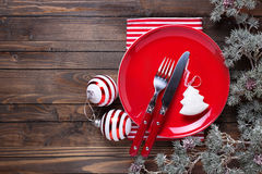 Red plate, knife and fork, napkin and christmas decorations in w Stock Photography