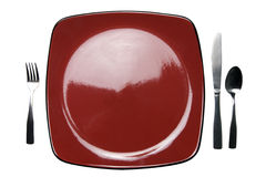 A red plate with knife fork spoon + clipping path. A red plate with knife, fork and spoon. Isolated on white with a clipping path Stock Image