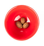 Red plate with nutmeg Stock Photo