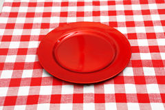 Red plate on red and white tablecloth Stock Image