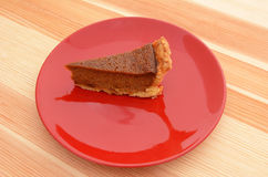 Red plate with a slice of pumpkin pie Royalty Free Stock Photography