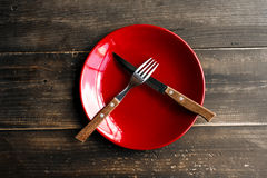 Red plate on the table with knife and fork. Spoon and fork on a plate crosswise Royalty Free Stock Images
