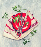 Red plate with vintage fork and knife on rustic napkin Stock Photography