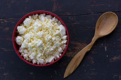 Red plate with white milky curd and juniper wooden spoon on an old black wooden table Royalty Free Stock Image
