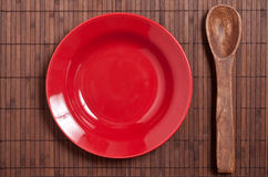 Red plate and wooden spoon Stock Image