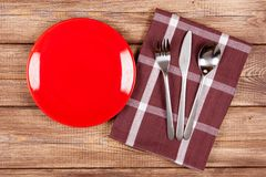 Red plate on a wooden table Royalty Free Stock Photos
