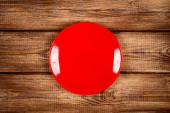 Red plate on a wooden table Stock Image