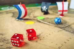Red playing bones on the world map of the field handmade Board games with a pirate ship. The game of battleship royalty free stock images