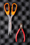 Red pliers and orange scissors on sponge Royalty Free Stock Photos