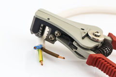 Red pliers stripping electrical wires. Red pliers stripping copper electrical conductors of different thicknesses Royalty Free Stock Image