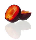 Red plum. Halves of red plum fruit isolated on white background Stock Images