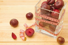 Red plum fruit with measuring tape Royalty Free Stock Photos