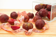 Red plum fruit with measuring tape in glass bowl Royalty Free Stock Image
