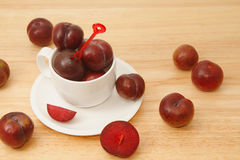 Red plum fruit in white cup Royalty Free Stock Image