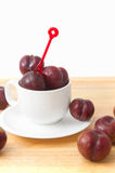 Red plum fruit  in white cup Royalty Free Stock Images