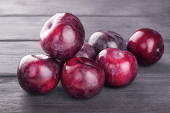 Red plum fruit on wooden. Background Stock Photo