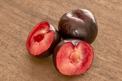 Red plum fruit. On wooden background Stock Photos